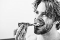 Young man resting at home with a nude and a pizza. Shirtless handsome young man with pizza on bed. Who cares about diet stock image
