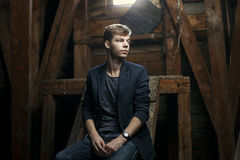 Young man resting in old church. Young man in an wodden attic Royalty Free Stock Images