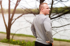 Young man resting after runing. looking on river. Stock Image