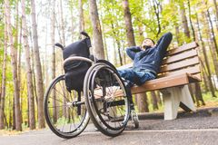Young man resting sitting on a bench with his legs on his wheelchair. stock image