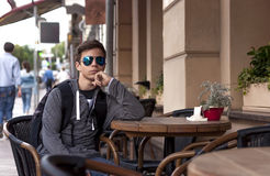Young man resting sitting at a table on a city street stock images