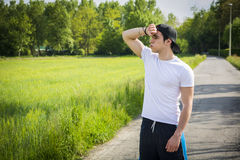 Young man resting standing in middle of the road Royalty Free Stock Image