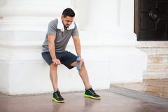 Young man resting after working out in the city. Attractive young man resting and drinking some water after exercising outdoors in the city Stock Image