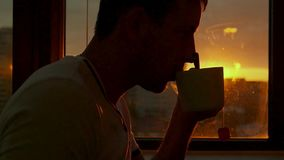 A young man rests in the evening at sunset and drinks hot tea by the window. HD, 1920x1080. slow motion. A young man rests in the evening at sunset and drinks stock video footage