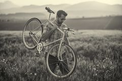 Young man with retro bicycle in sunset on the road, fashion photography on retro style with bike Stock Images