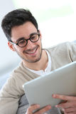 Young man with retro eyeglasses using tablet Stock Photography