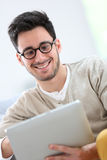 Young man with retro eyeglasses websurfing Royalty Free Stock Photos