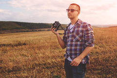 Young Man with retro photo camera outdoor hipster Lifestyle Royalty Free Stock Images