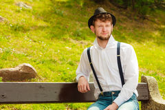 Young man retro style sitting on bench in park Royalty Free Stock Photography