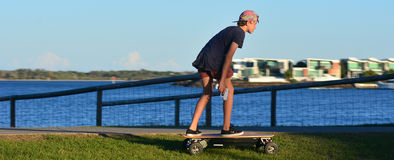 Young man rid on motorized skateboard. GOLD COAST - OCT 14 2014:Young man rid on motorized skateboard.It's a four wheel drive motorised skateboard capable of Royalty Free Stock Images