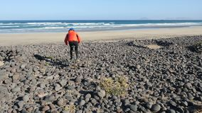 Young man rides a bicycle on big stones towards a sand beach on Canary Islands. Lanzarote, Atlantic ocean. Lanzarote, Atlantic ocean. Young man rides a bicycle stock footage