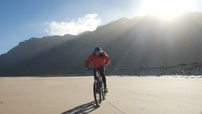 Young man rides a bicycle on a sand beach on Canary Islands. Lanzarote, Atlantic ocean. Young man rides a bicycle on a sand beach on Canary Islands. Lanzarote stock footage