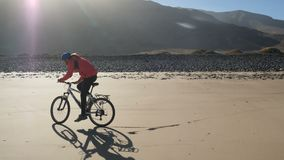 Young man rides a bicycle on a sand beach on Canary Islands. Wheelie trick on a sand, Lanzarote, Atlantic ocean. Young man rides a bicycle on a sand beach on stock footage