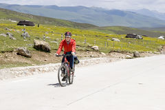 Young man rides bike. Young man with red clothes riding bike Royalty Free Stock Photos