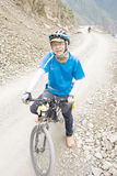 Young man rides bike. Young man with blue clothes riding bike in mountain road Royalty Free Stock Images