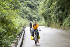 Young man rides bike. In mountain road Royalty Free Stock Photo
