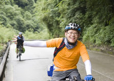 Young man rides bike. In mountain road,waving his hands Royalty Free Stock Images