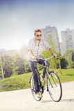 Young man riding bicycle. Businessman riding a bicycle to work Stock Photo