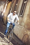 Young man riding bicycle. Businessman riding a bicycle to work Royalty Free Stock Photo