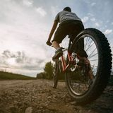 Young man riding bicycle along a country road. Cycling. Low angle view of young man riding bicycle along a country road in sunset light. Bicycle sports Stock Photography