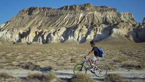 Young man riding a bicycle on a background of a landscape with mountains stock video footage