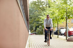 Young man riding bicycle on city street. Lifestyle, transport and people concept - young man riding bicycle on city street Royalty Free Stock Image
