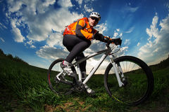 Young man riding on bicycle through deep grass with backpack Royalty Free Stock Photo