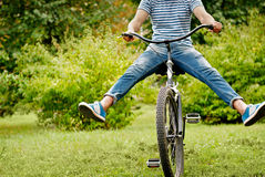 Young man riding bicycle with her legs in the air Stock Photo
