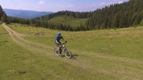 Young man riding a bicycle on the high plateau stock video