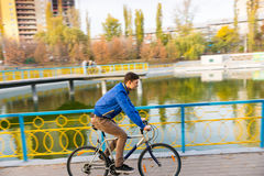 Young Man Riding Bicycle near Water in Autumn Stock Image