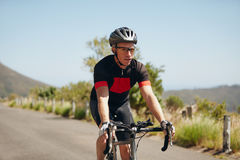 Young man riding bicycle on open road Stock Photography