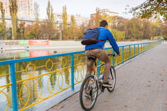 Young Man Riding Bicycle Through Park in Autumn Royalty Free Stock Image