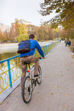 Young Man Riding Bicycle Through Park in Autumn Royalty Free Stock Photography
