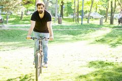 Young man riding a bicycle. In the park in summer Stock Image