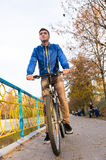 Young Man Riding Bicycle on Path Through Park Royalty Free Stock Image