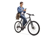 Young man riding a bicycle and using a phone. Isolated on white background Royalty Free Stock Photography