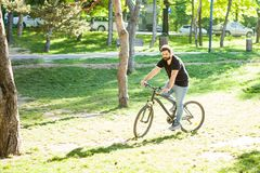 Young man riding a bicycle. In the park in summer Stock Images