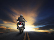 Young man riding big bike motocycle on asphalt high way against. Beautiful dusky sky use for biker traveling and journey theme Royalty Free Stock Image