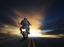 Young man riding big bike motocycle on asphalt high way against. Beautiful dusky sky use for biker traveling and journey theme stock image