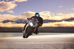 Young man riding big bike motorcycle against sharp curve of asph Stock Photos