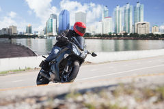 Young man riding big bike motorcycle on city road against urban. And town building scene background use for people and convenience vehicle to traveling in town stock photo