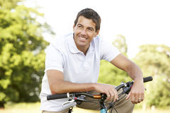 Young man riding bike in countryside Royalty Free Stock Images