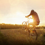 Young man riding a bike at sunset Stock Image