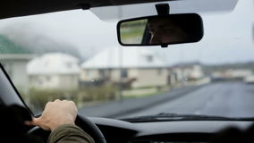 Young man riding the car through the empty streets. Tourists man exploring the city. Male eyes reflected in the mirror. Young man riding the car through the stock footage