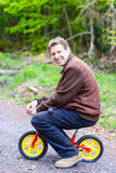 Young man riding on child bike in forest Royalty Free Stock Photo