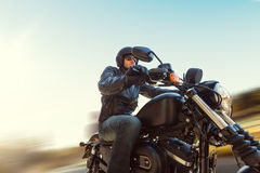 A young man riding a chopper on a road Royalty Free Stock Image