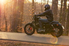 Young man riding chopper on road in forest Royalty Free Stock Photography