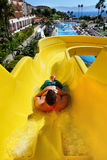 Young man riding down a water slide. Young man riding down a yellow water slide stock image