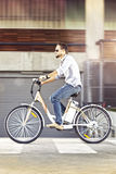 Young man riding electric bicycle. Young man riding a electric bicycle to work royalty free stock image