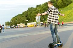 A young man is riding a electric scooter on the embankment. The summer evening. stock photo